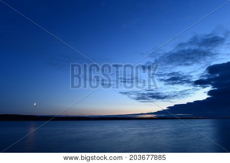 Moonrise in the blue sky above the water surface of the lake