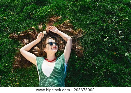 A joyous fashionable woman in sunglasses lies on a lawn with bright green grass
