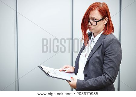 Business Concept Of Success And Growth. A Woman Boss, In A Suit And Wearing Glasses, Holds A Tablet