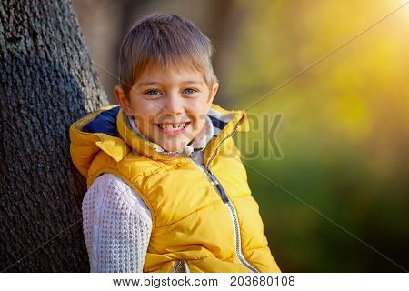 Clouse up portrait of happy boy having fun in the autumn park with golden leaf