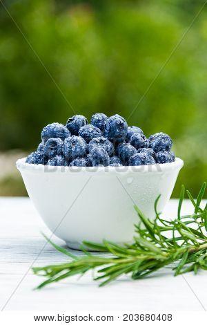 Juicy organic blueberries on white table. Useful breakfast