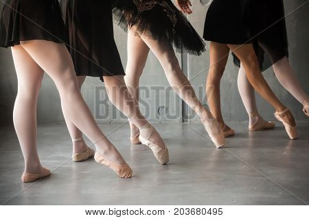 close-up of a young ballet dancer in black dresses white pantyhose and pointe shoes pull a sock