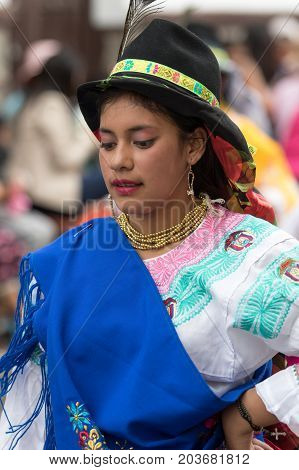 June 17 2017 Pujili Ecuador: young indigenous woman in bright color traditional clothing at Corpus Christi parade dancing in the street