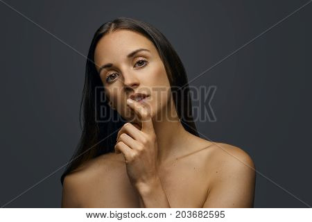Attractive young woman with bare shoulders looking thoughtfully at the camera with her finger to her chin and head tilted to the side over a grey background