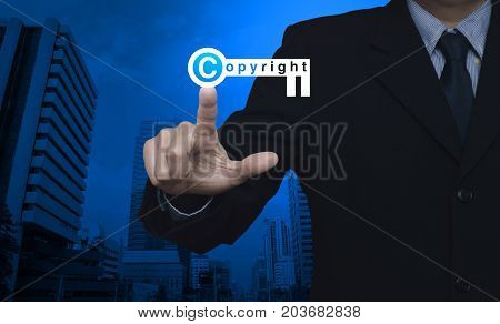 Businessman pressing copyright key icon over modern office city tower Copyright and patents concept