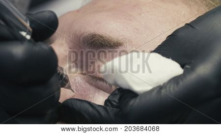 Extreme close up. Permanent make-up of dark circles under the eyes. Tattooing of dark circles in beauty clinic.