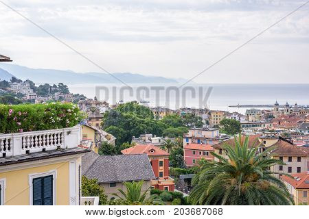 Morning view from above to cloudy day in Santa Margherita Ligure city and sea in Italy. Balcony full of flowers.