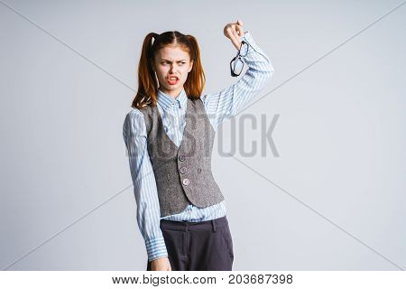 A woman teacher holds fast her glasses in disgust. Isolated on a gray background