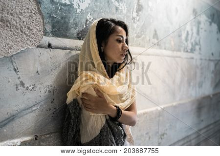 Portrait of a thoughtful sad girl in a headscarf on the head of the light sitting in the temple, praying