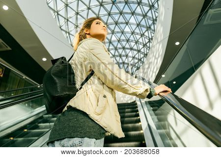 A beautiful girl with lush blond hair rises on an escalator, looks somewhere