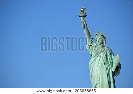 Statue of liberty in a deep blue sky, from Liberty Island in New York City Bay