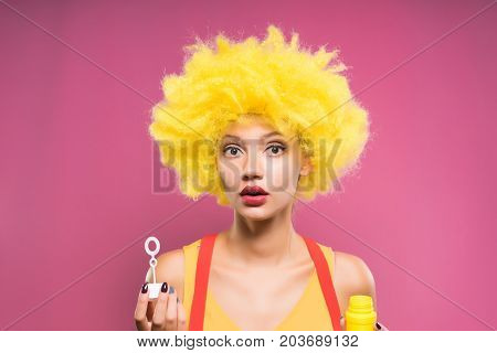 A woman clown in a yellow wig is puzzled with soap bubbles. Isolated on a pink background