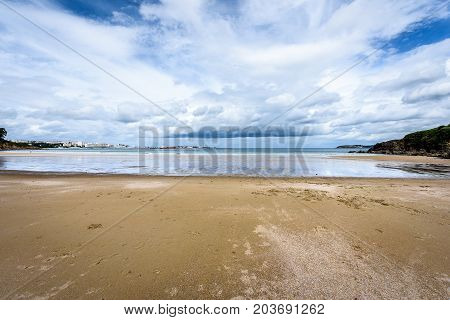 Atlantic Sandy Beach In Spain With City Of Coruna Background.