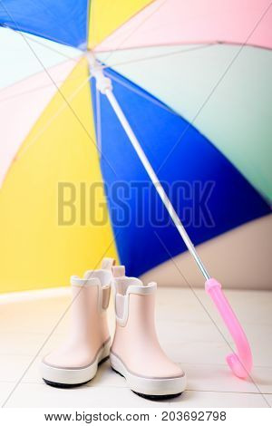 Pink little children rubber boots stand under colorful umbrella concept of autumn or spring background.