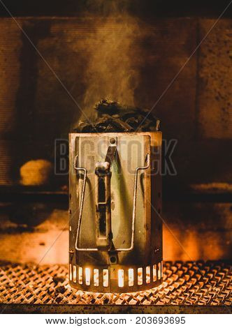 Preparing barbecue coals or briquettes in chimney starter at night. Starting up coals for bbq inside of fireplace with special fire starter. Flames on the bottom and smoke on the top.