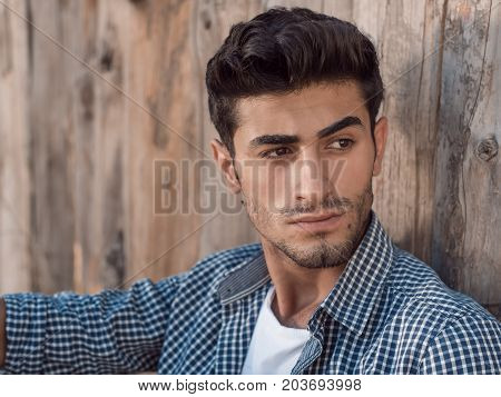 Portrait of confident young man with facial hair sitting against wooden wall looking away. Handsome man wearing shirt t-shirt and jeans resting outdoors