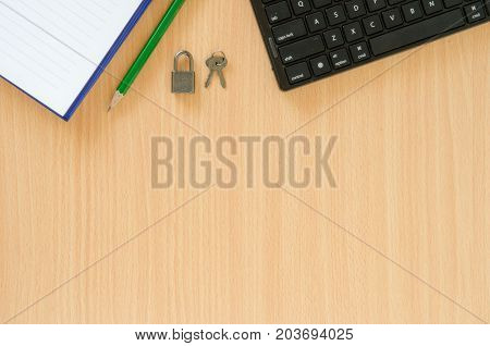 White note book and green pencil and black keyboard and key on beech color background with copy space.