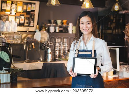 Smiling asian woman barista holding blank tablet compute in front of coffee shop counter barMock up space for display of menu or designclipping path on screen