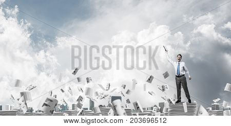 Businessman keeping hand with book up while standing among flying paper documents with cloudly sky on background. Mixed media.