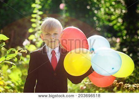 Cute boy going back to school. Boy in the suit. Child with colorful balloons on first school day.