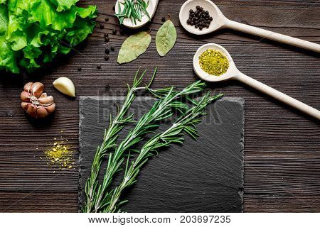 spices for cooking and fresh herbs, salad on wooden table top view