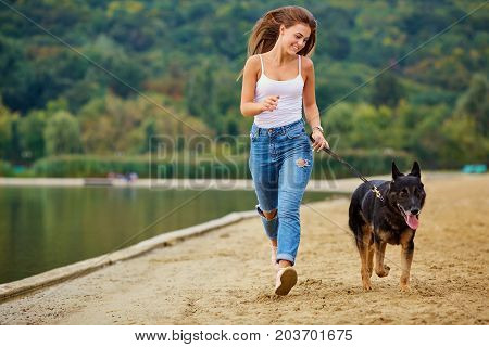A girl is playing with her dog on the beach in summer park. A woman with a German shepherd runs through the sand.