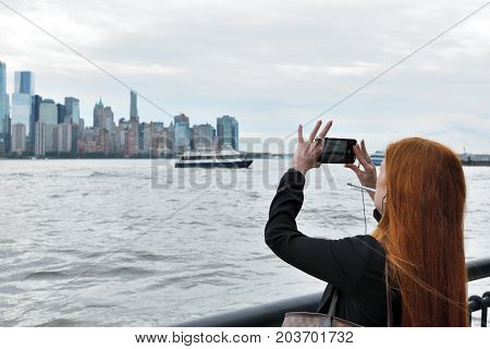 JERSEY CITY USA - AUG. 23 : Unidentified people taking photo of Manhattan on August 23 2017 in New York City NY. Manhattan is the most densely populated borough of New York City.