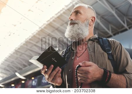 Low angle side view calm old beard man looking through holy book in airport. He is praying for good flight