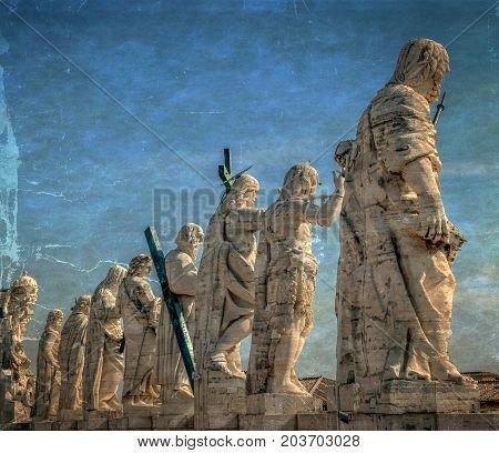 Old photo with back view of statues of the saints apostles located on the top of St Peter Basilica roof. Vatican City Rome Italy. Vintage processing.