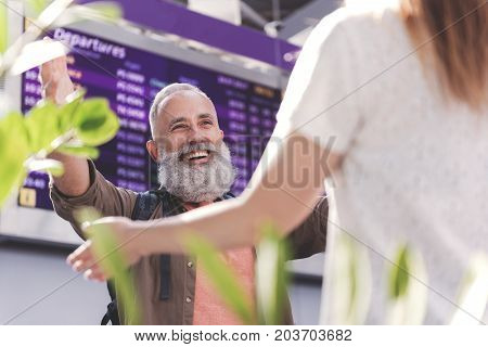 Low angle portrait of cheerful bearded old man meeting young girl near timetable in big apartment. He is raising hands for hug