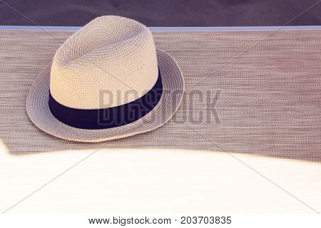 The summer hat on the beach lounge chair near the sea