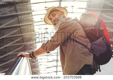 Low angle portrait of outgoing bearded grandfather situating on escalator. He holding luggage