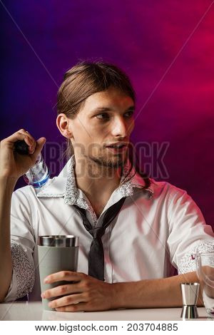 Alcohol liquor entertainment relax bartending concept. Barman fills shot glass. Young male bartender makes a drink.
