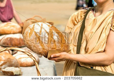 Bread Seller Woman Holding Big Round Loaf Of Bread In Her Arms