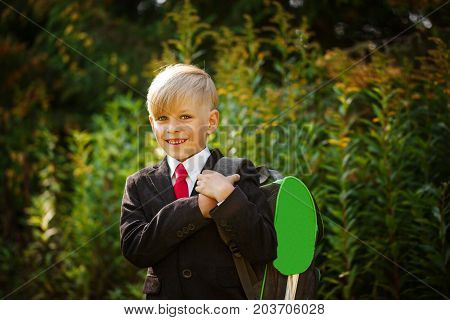 Cute boy going back to school. Boy in the suit. Closeup portrait of smiling pupil with backpack on first school day.