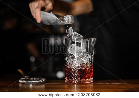 Barman puts the ice cubes into a glass with a red cocktail