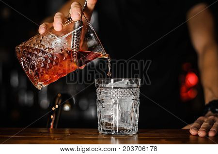 close up of bartender pouring bright red alcohol cocktail into the glass with ice