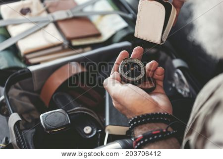 Close up male pensioner hand holding direction finder while sitting in airport. Journey concept