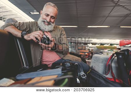 Low angle portrait of outgoing unshaven grandfather holding photographic apparatus in hand while sitting in concourse. Journey concept