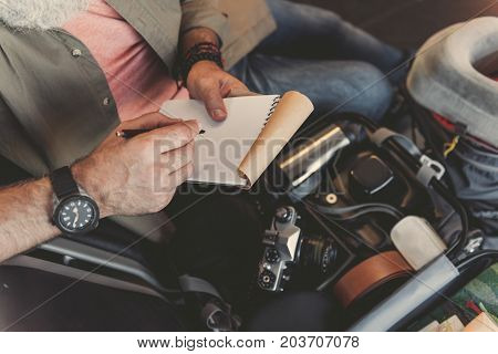 Top view close up pensioner hand writing in notebook while sitting near open suitcase with different objects for journey