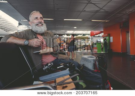 Portrait of cheerful bearded old man making notes in sketchbook while locating on comfortable chair in waiting room in airport