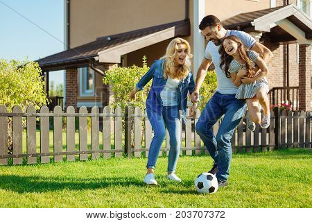 Quality time together. Happy cheerful father carrying his adorable little daughter in his arms while playing football with his family in the backyard