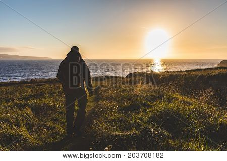 Man with backpack walking toward the sea at sunset. Explorer hiking over a cliff next to the seaside backlight shot. Nature and adventure concepts.