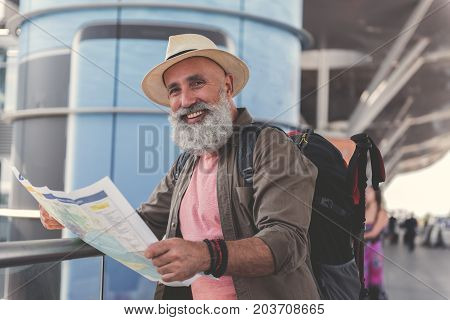 Cheerful elder bearded tourist wearing hat is holding unfolded map and looking at camera with bright smile. Waist up portrait