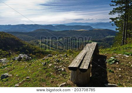 Viewpoint with a bench at mount Bobija, beautiful view of surrounding peaks, hills, meadows and colorful forests, west Serbia