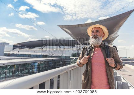 Glad bearded male person is carrying backpack and looking ahead with bright smile. He standing near airport. Waist up portrait. Copy space on left side
