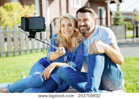 Capturing moments. The focus being on a sefie stick in the hands of a beautiful woman sitting bonding to her beloved husband while taking a selfie together on backyard picnic
