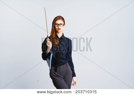 A young strict woman teacher in glasses with red hair is holding a pointer in her hand. Isolated on white background