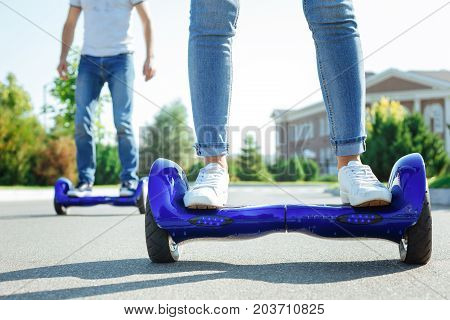 Cutting-edge technology. The close up of female legs standing on a blue self-balancing scooter while a man riding another one in the background