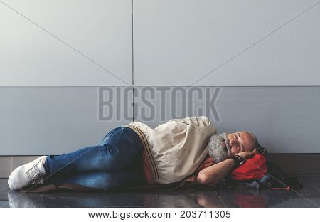 Glad mature bearded tourist is sleeping near wall. He putting head on red backpack. Copy space